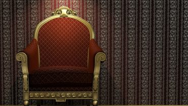 golden-and-red-classic-armchair-under-a-bright-spotlight